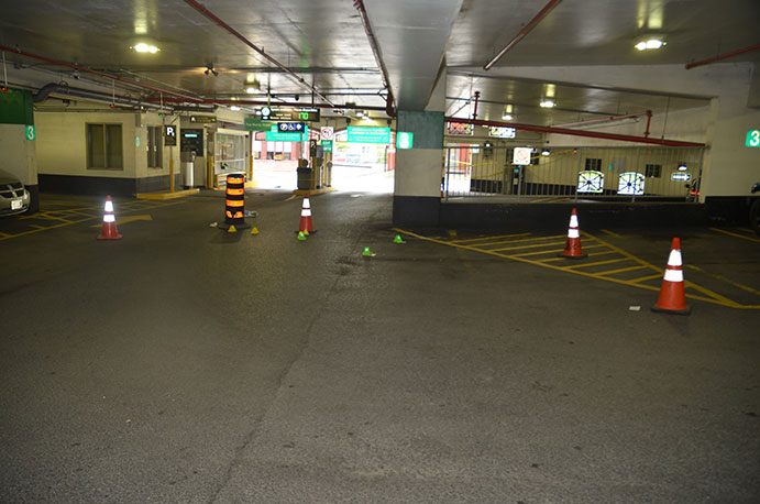 This is an image of a parking garage with markers placed on the floor depicting evidence locations for case 17-OFD-135.