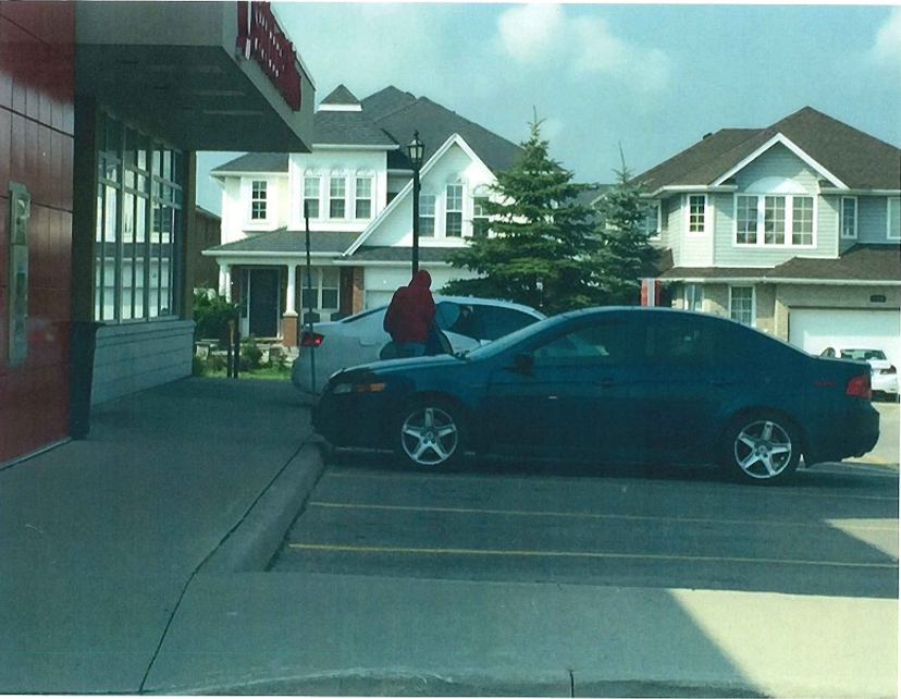 A photo taken by a civilian witness following the attempted robbery at the Scotia Bank.  This photos depicts the alleged robbers re-entering their vehicle.