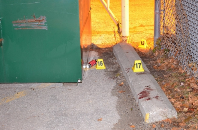A grey hooded sweater and a canister of bear repellent spray were located behind the two industrial garbage bins