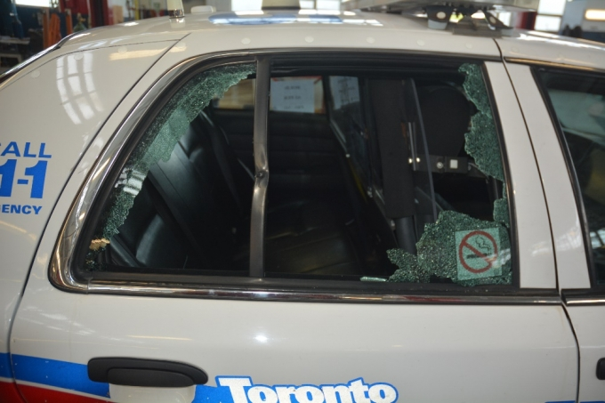 The rear window of WO #2 and WO #3's police cruiser which shattered when it was struck by a bullet. A projectile was found lodged in the bent portion of the frame.