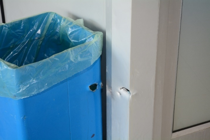 Apparent bullet hole through garbage can and corner of security office.