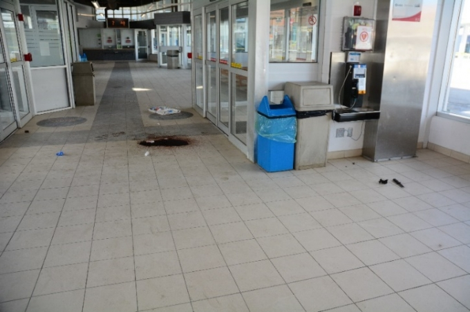 One of the Complainant's knives is seen on the floor to the right of the photo; the blood pooling indicates the location where the Complainant fell after being shot.  (The entrance doors are to the right in the photo and the security office to the left.)