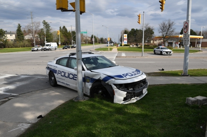 This photograph faces south from the west side of the west sidewalk of Dixie Road depicting the right front corner of PRP vehicle.  The damage to the right front fender is evident.  Damage to the right rear fender indicates a secondary impact.