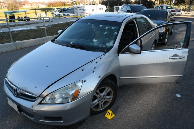 The Complainant's Honda Accord with several bullet holes visible on the front left quarter panel, hood and windshield.