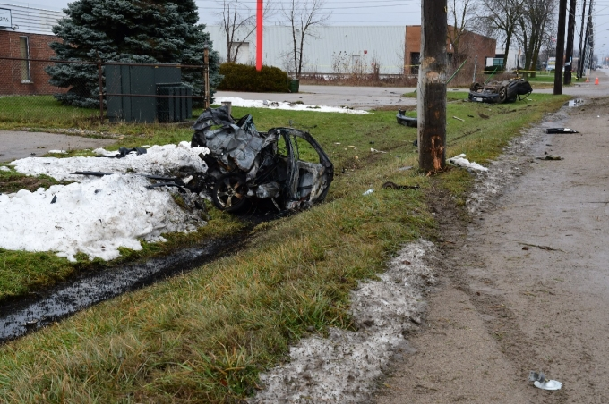 Tire marks are visible leading up to a damaged utility pole. The rear half of the Mazda rests in the foreground with scorch marks on the ground nearby. The front half of the Mazda rests on its roof in the background. Vehicle debris scatters the area.