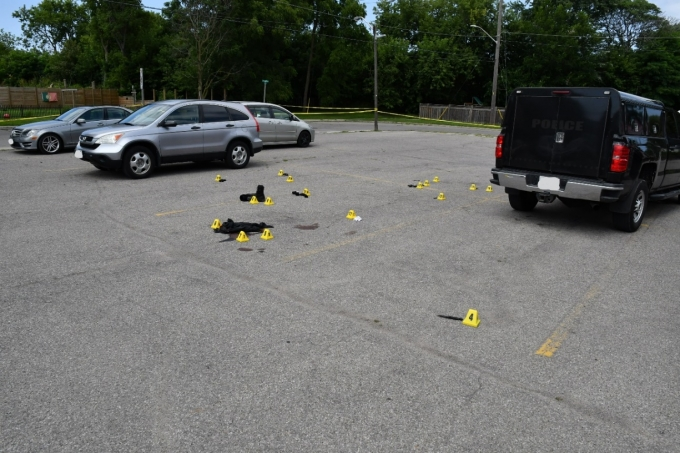 Figure 1 - The parking lot where the shooting occurred. Yellow evidence markers indicate where items, including cartridge cases, knives, CEWs and the Complainant's personal belongings, were found.