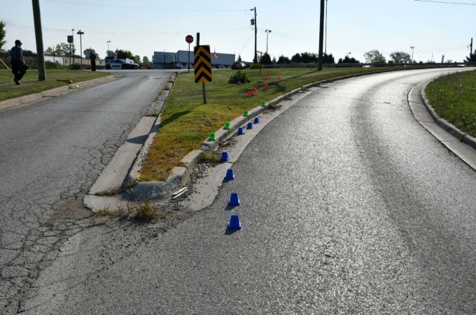Figure 2 - This photograph was taken by SIU FI and faces east on Campbell Street where the southbound ramp to Indian Road South commences. The blue cones depict the tire mark made by the front tire and the green cones depict the tire mark made by the rear tire of the Kawasaki motorcycle. The orange cones depict the gouges in the grass. The red circle depicts the resting location of the Kawasaki motorcycle.