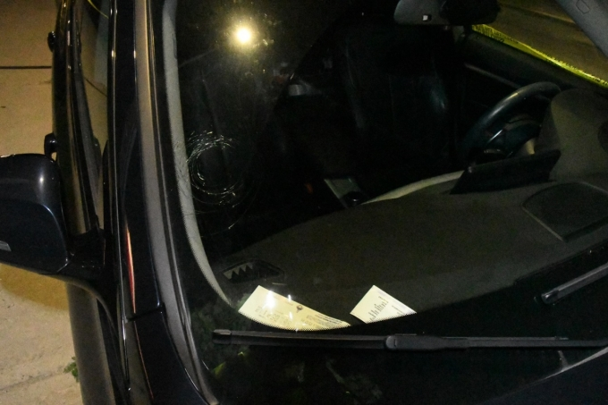 Figure 2 - The windshield of a black BMW at the scene with damage from what appears to be a bullet strike.